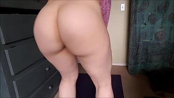 Молодая блондиночка в красном пеньюаре позирует перед камерой